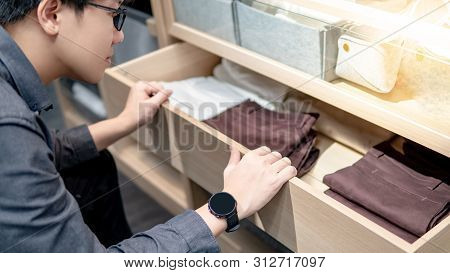 Asian Man Wearing Glasses Opening Closet Drawer Choosing Pants Or Trousers For Dressing Up. Home Lif