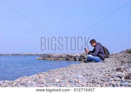 Man Traveller Is Sitting On Sea Stone Beach And Browsing Smartphone, Side View. Guy On His Spring Va