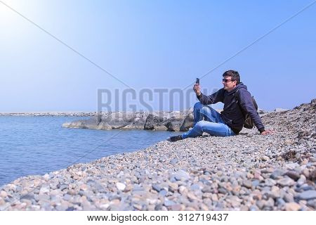 Man Talks Video Chat In His Smartphone Sits On Sea Stone Beach On Vacation. Guy Tourist On Vacation.