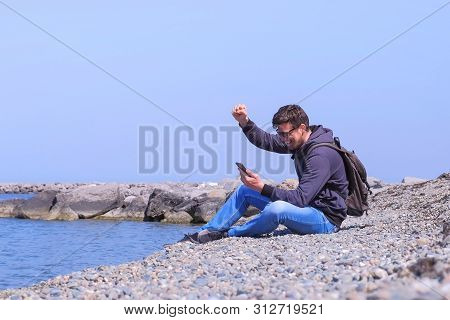 Successful Young Man Is Happy About Getting Great News On Smartphone. Guy Is Sitting On Sea Stone Be