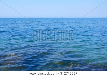 Seascape With Transparent Blue Water, Stones And Clear Sky At Sunny Day. Nature Background With Sea