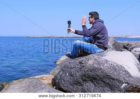 Man Traveller Talks Video Chat On Smartphone Sits On Sea Stone Beach On Vacation. Mobile Phone With