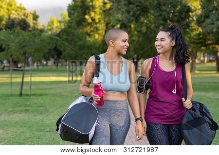 Young female friends talking after workout routine in park. Two curvy women in a conversation holding gym bag outdoor. Smiling multiethnic woman relaxing after fitness exercise at park.