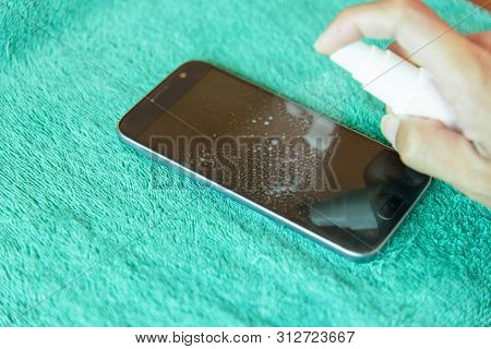 Spray The Chemical Solution To Cleaning The Smartphone