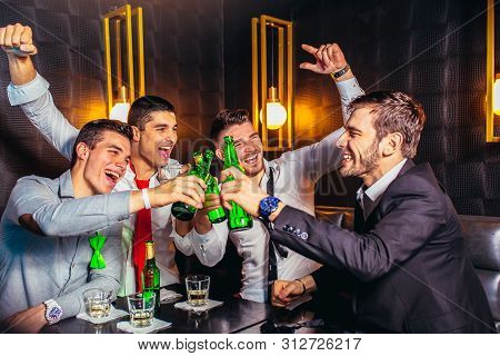 Group Of Young Men Toasting At A Nightclub