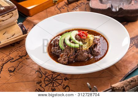 Braised Beef Served On White Plate With Chili Pepper And Avocado On Old Map Background Side View