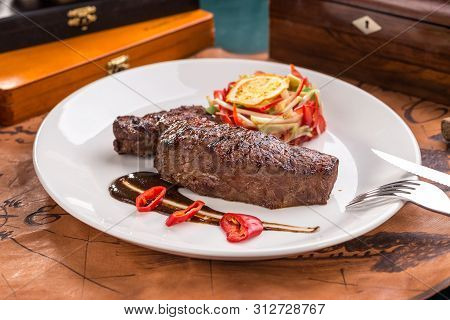 Grilled Beef Steak With Fresh Vegetable Salad And Chili Pepper On White Plate On Old Map Background