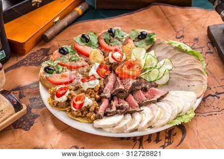 Different Appetizer And Smoked Meat On The Plate On Old Map Background Side View