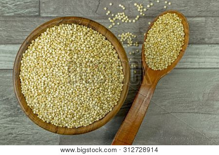 A Flat Lay Image Of A Bowl Of Quinoa With Spoon On A Wooden Background Surface