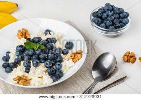 Healthy Breakfast. Cottage Cheese With Blueberry, Nuts, Honey And Mint In A White Bowl On A White Ba