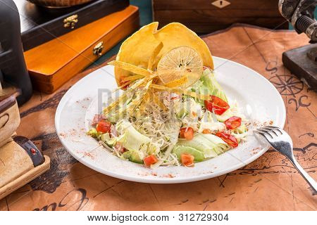 Healthy Grilled Chicken Caesar Salad With Parmesan Cheese And Chips On Old Map Background Side View