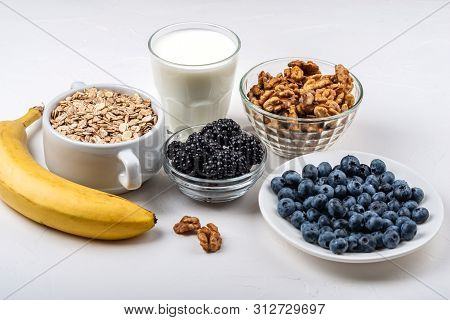 Ingredients For The Healthy Breakfast. Oatmeal, Milk, Blackberry, Blueberry, Bananas, Walnuts On The