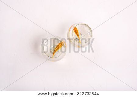 Lonely Fish Swim In Their Wine Glasses. Pets Are Separated. Goldfish In Water On A White Background.