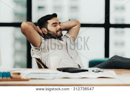 Relax Time.  Successful Businessman Relaxing  And Resting After Sitting And Hard Working In Modern O