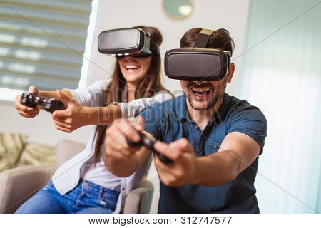 Young Happy Couple Playing Video Games Virtual Reality Glasses. Couple Having Fun With New Trends Te
