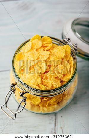 Corn Flakes In A Glass Jar On Wooden Surface