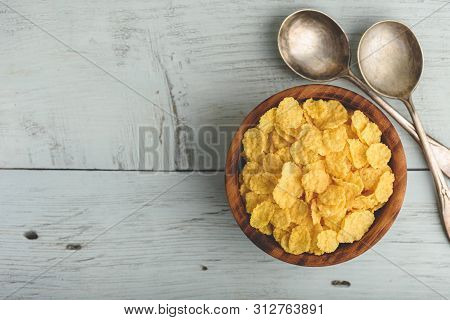 Rustic Bowl Of Corn Flakes Over Wooden Surface. View From Above