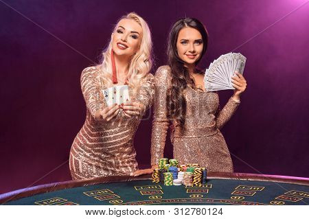 Beautiful Girls With A Perfect Hairstyles And Bright Make-up Are Posing Standing At A Gambling Table