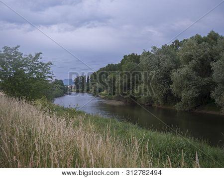 River Vah With Trees, Grass And Reeds On Borders In Liptovsky Mikulas Near Lake Liptovska Mara, Slov
