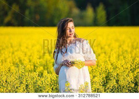 Pregnant Girl Holding Flowers. Belly Of A Pregnant Woman. The Concept Of Pregnancy. Over Green Natur