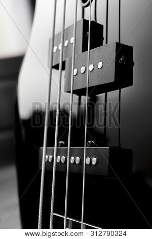 Close-up Bass Guitar Pickups And Strings. Musical Instruments. Black Guitar Deck.