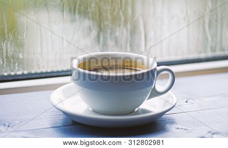 Wet Glass Window And Cup Of Hot Coffee. Autumn Cloudy Weather Better With Caffeine Drink. Enjoying C