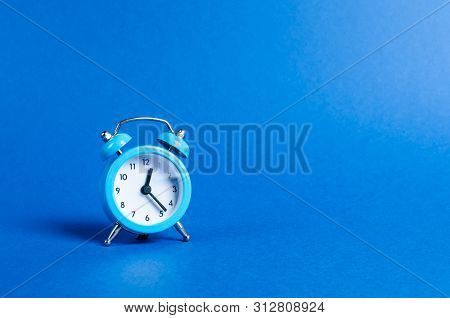 A Blue Alarm Clock On A Blue Background. Limited Offer And Over Time. Planning And Discipline. Waiti