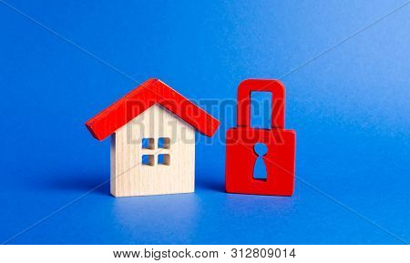 A Wooden House And A Red Padlock. Unavailable And Expensive Real Estate. House Insurance. Security A