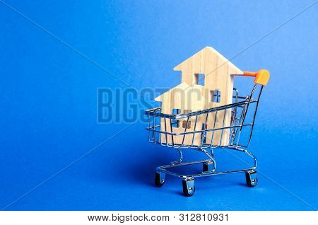 Wooden Houses In A Trading Cart. The Concept Of Buying A House Or Apartment. Affordable Housing. Pro