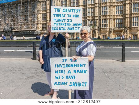 London / Uk - June 26th 2019 - Two Women Hold Signs Outside Parliament About Climate Change As Part