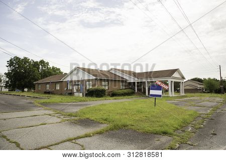 A Rundown Residential And Commercial Property In A Suburban Area With A For Lease Sign.