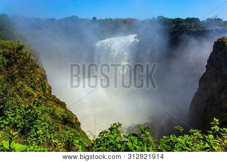 The waterfall Victoria Falls located on the Zambezi River. Giant cloud of water fog over waterfall. Victoria National Park. Journey after the wet season. Concept of extreme and photo tourism