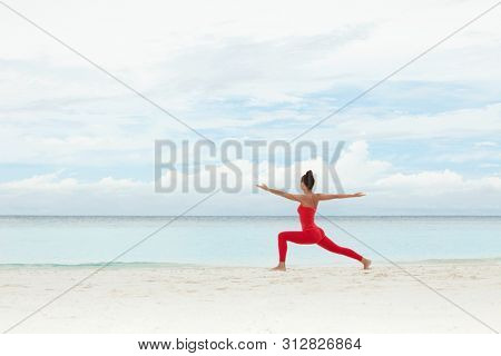 Yoga outdoor. Happy woman doing yoga exercises, meditate on the beach. Yoga meditation in nature. Concept of healthy lifestyle and relaxation. Pretty woman practicing yoga near the sea