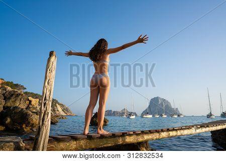 Ibiza cala d Hort girl open arms on pier sunset Es Vedra islet Balearic Islands