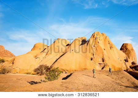 Kids brother and sister hiking in Spitzkoppe with unique rock formations in Damaraland Namibia