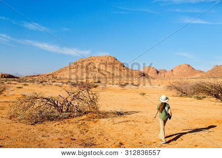 Young girl hiking in Spitzkoppe with unique rock formations in Damaraland Namibia