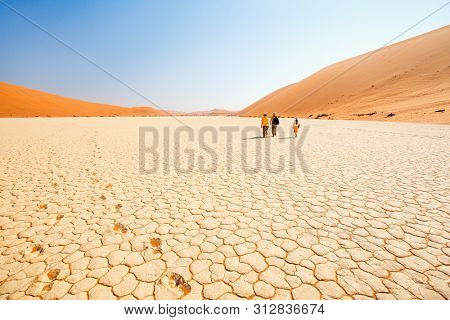 Back view of family father and two kids walking at white clay pan surrounded by red dunes in Deadvlei in Namibia
