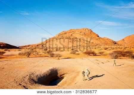 Family mother and two kids hiking in Spitzkoppe area with unique rock formations in Damaraland Namibia