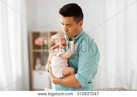 family, parenthood and fatherhood concept - middle aged father comforting little baby daughter at home