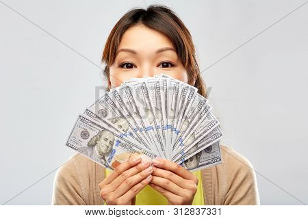 people, ethnicity and portrait concept - happy asian young woman holding hundreds of dollar money banknotes over grey background