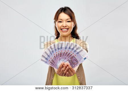 people, ethnicity and portrait concept - happy asian young woman holding hundreds of euro money banknotes over grey background
