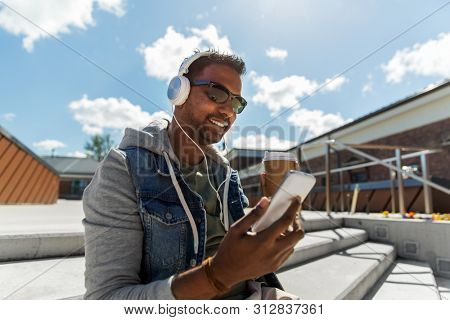 technology, leisure and people concept - indian man with headphones listening to music on smartphone on roof top