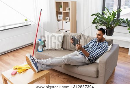 people, housework and housekeeping concept - smiling indian man in headphones listening to music on tablet computer after home cleaning