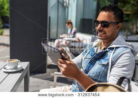 travel, tourism and lifestyle concept - indian man with tablet computer and coffee at city street cafe