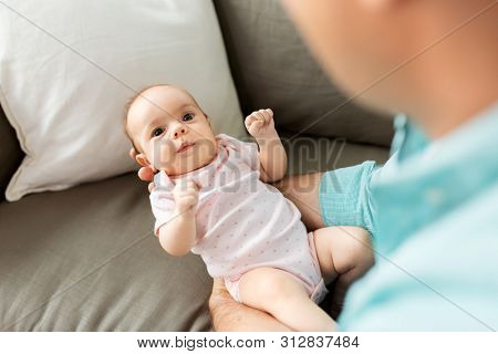 family, parenthood and fatherhood concept - close up of middle aged father with little baby daughter at home