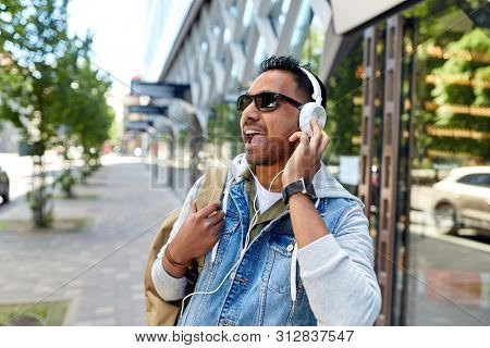 travel, tourism and lifestyle concept - smiling indian man in headphones with backpack listening to music on city street