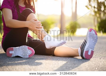 Ankle Sprained. Young Woman Suffering From An Ankle Injury While Exercising And Running. Healthcare