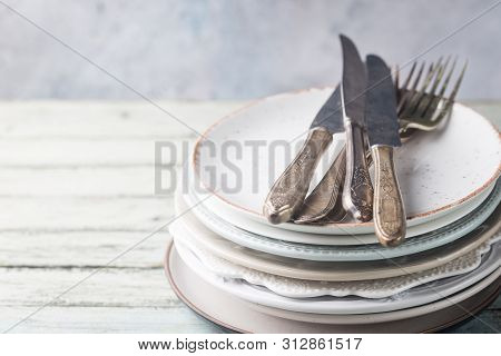 Stack Of Clean Dinner Plates With Cutlery On Top Over Wooden Table. Pastel Tones.