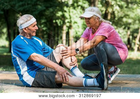 Retired Upset Woman Touching Knee Of Senopr Man While Sitting On Walkway In Park