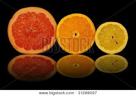 The Sliced Fruit And Their Reflection On A Black Background